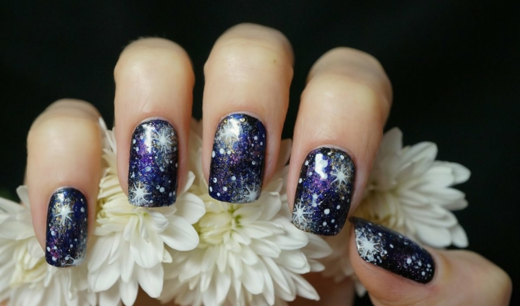 Idea per delle unghie capodanno con un effetto stellato con fiori bianchi in mano