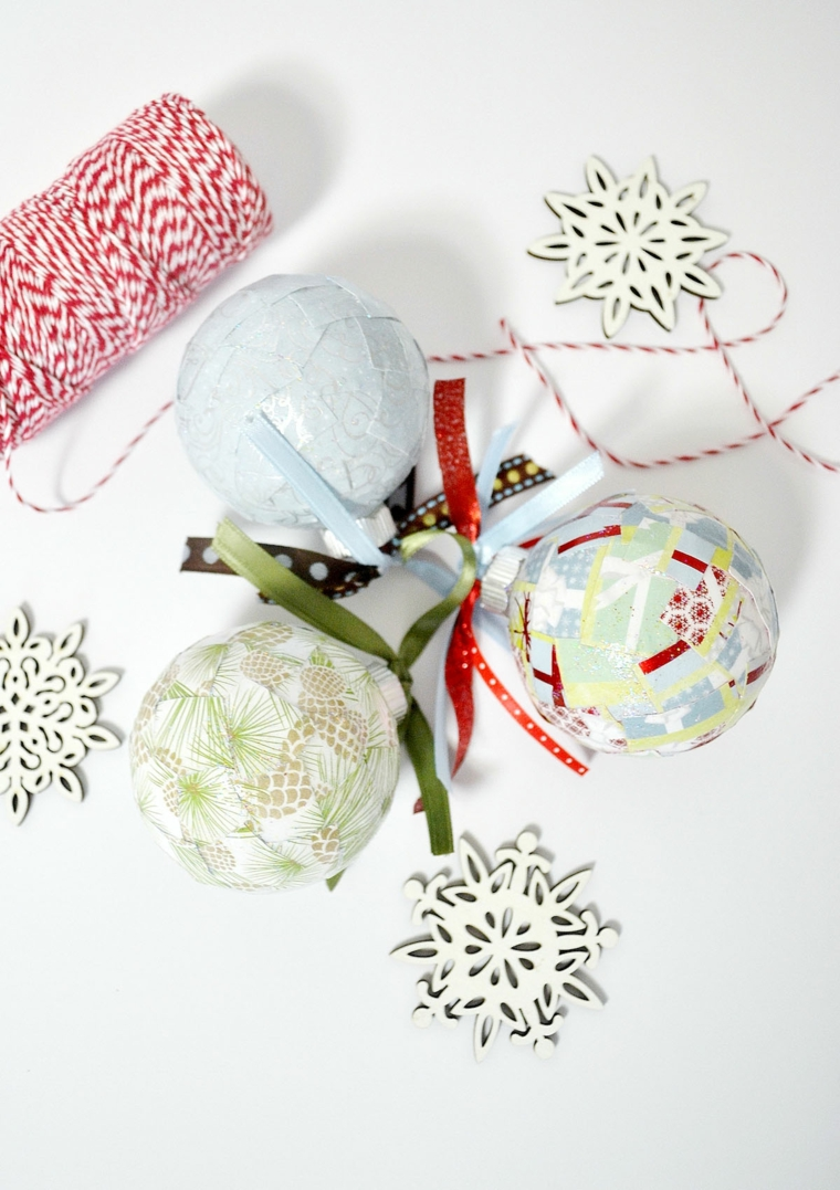 Idea per decorare le palline di Natale con carta colorata da appendere con un filo bianco e rosso