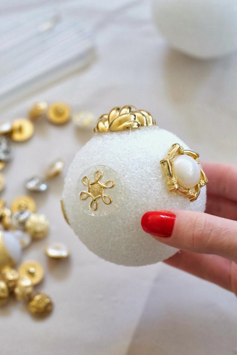 Una pallina natalizia di polistirolo con ornamenti di oro da appendere all'albero