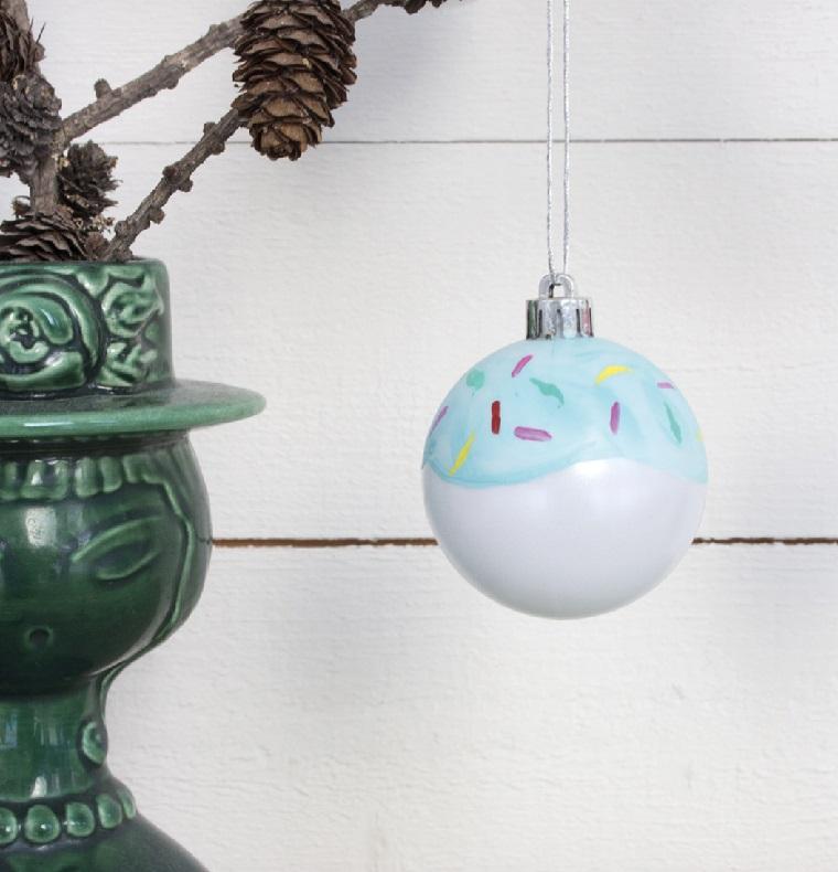 Creazioni di Natale fatte a mano, una pallina dipinta appesa su un albero con pigne