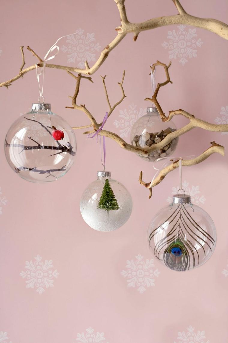 Sfere trasparenti appese ad un ramo, palline dipinte e decorate per Natale