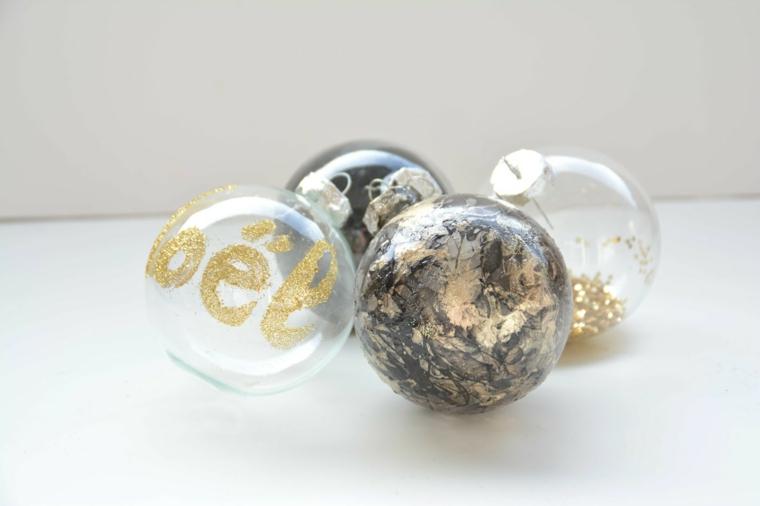 Semplici decorazioni con scritte e disegni su palline trasparenti da appendere all'albero di Natale