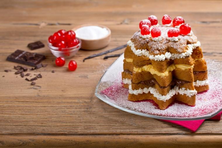 Dolce natalizio e un pandoro tagliato a fette con panna montata all'interno e decorato con ciliegie