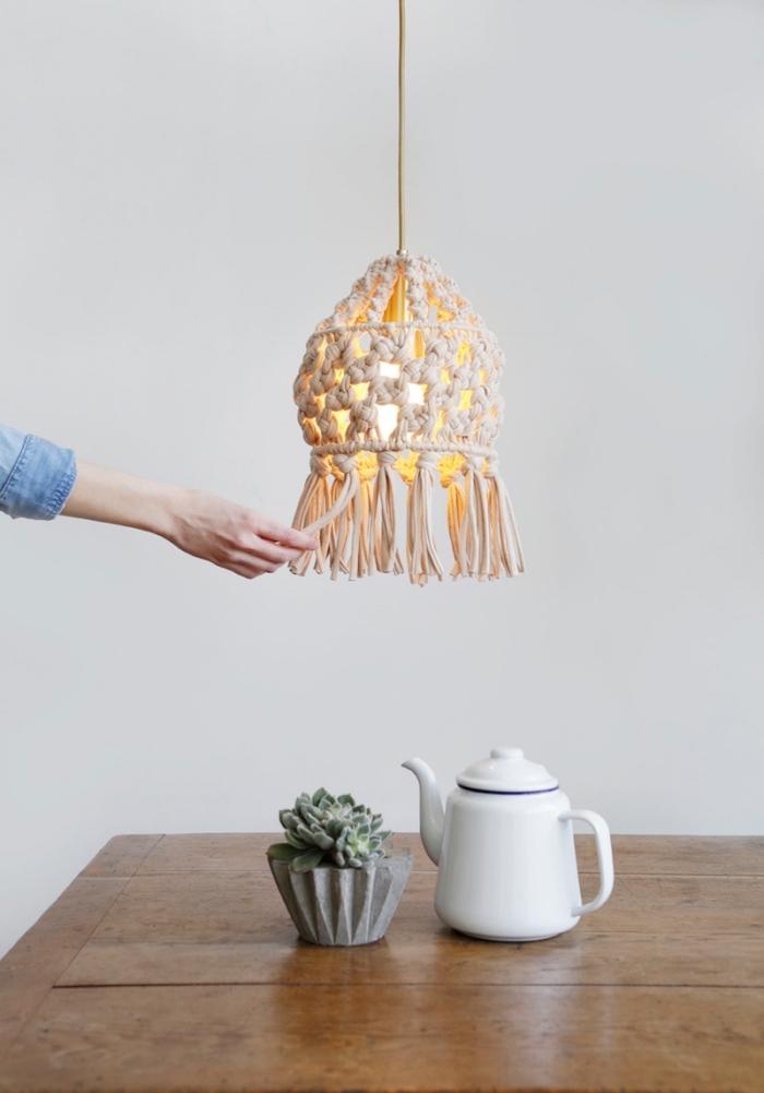 Un lampadario decorato con un paralume di macramè, tavolo di legno con piantina grassa