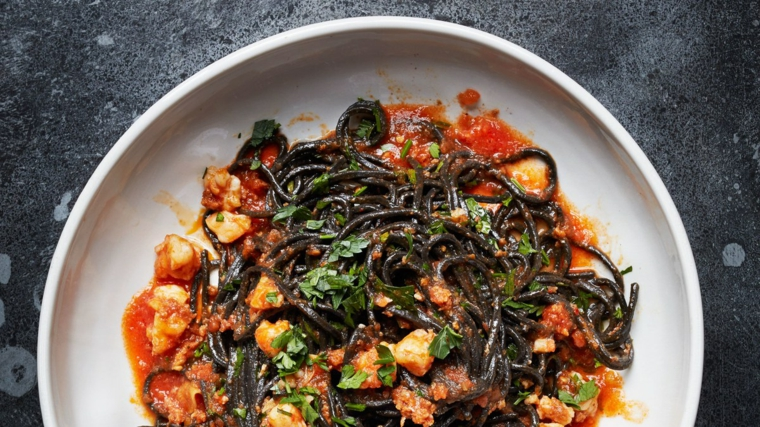 Spaghetti di colore nero con pesce e salsa di pomodoro per un secondo natalizio