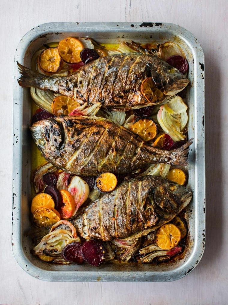 Teglia con tre pesci preparati al forno con verdure colorate
