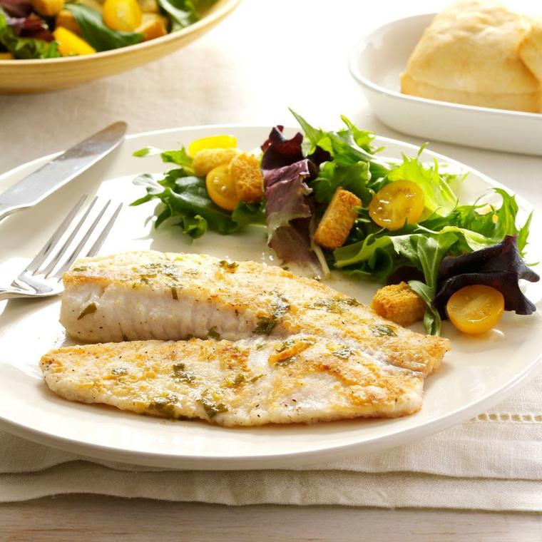 Seconda portata con un filetto di tilapia e contorno di insalata verde e pomodorini gialli