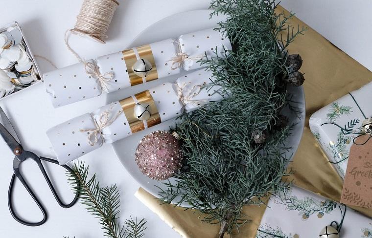 Un'idea per incartare i regali con rotoli di carta igienica e decorati con rametti verdi