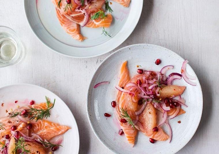 Piatto con filetti di salmone e cipolla rossa a fette, decorazione con chicchi di melograno