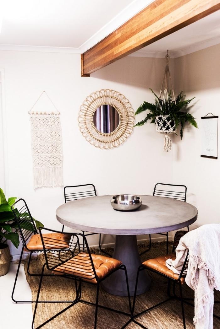 Una sala da pranzo con un tavolo rotondo e decorazioni da parete con trecce di corda