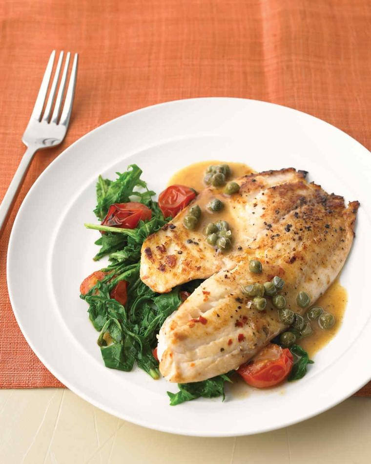 Filetto di pesce bianco con contorno di spinaci, pomodorini e capperi