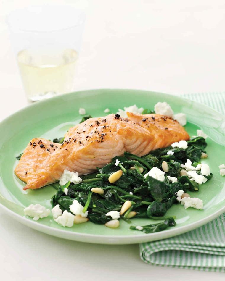 Filetto di salmone al forno con contorno di spinaci e pinoli, formaggio sbriciolato sul piatto