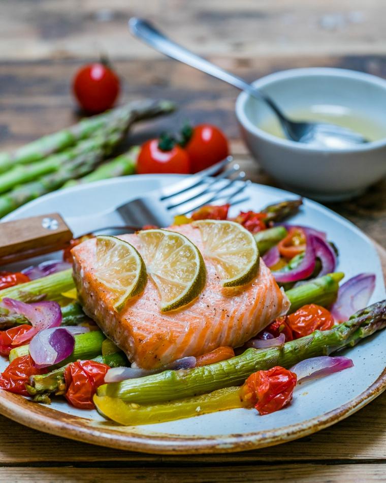 Menu Vigilia di Natale con un piatto di filetto di salmone con contorno di asparagi e pomodorini