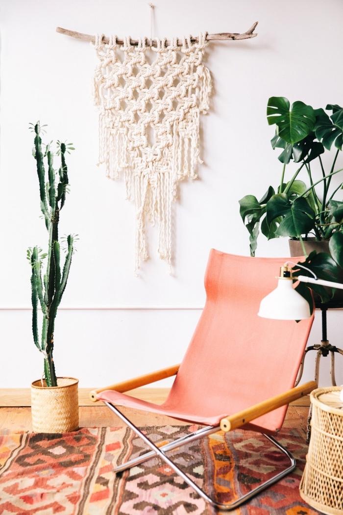 Soggiorno con una sedia di colore rosa e una decorazione in macramè