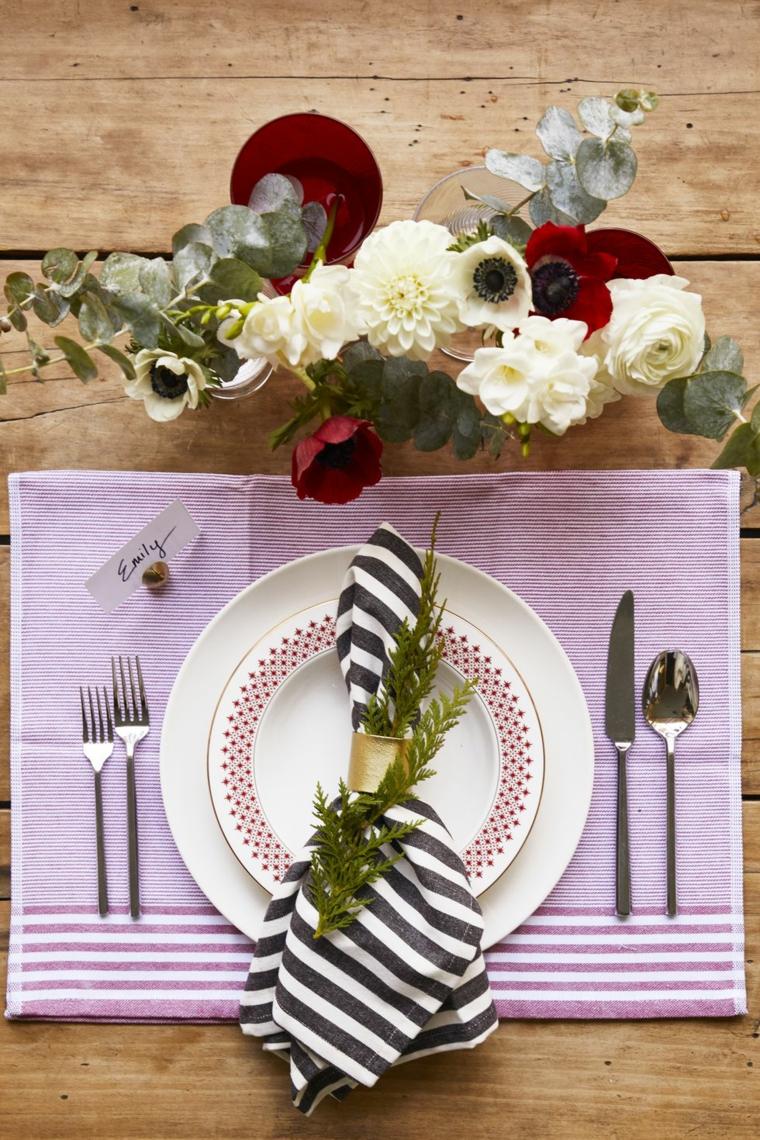 Tavolo apparecchiato con un segnaposto natalizio, fiori e rametti per la decorazione
