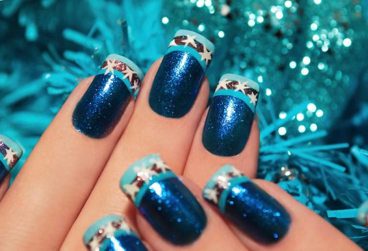 Nail art natalizie con unghie dipinte di blu glitter e french manicure con disegni di stelle