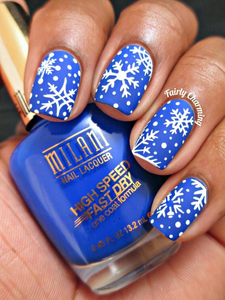 Nail art natalizio con smalto di colore blu e disegni di fiocchi di neve e puntini bianchi