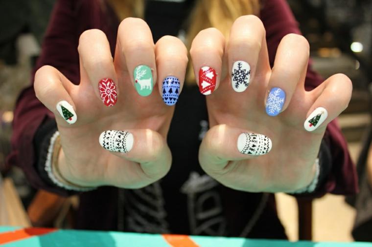 Mani donna che sfoggia una manicure natalizia con disegni e motivi colorati