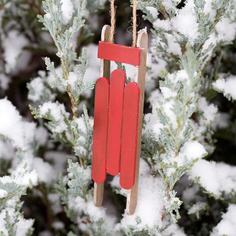 Una slitta con bastoncini di legno colorati, idee natalizie da creare per addobbare l'albero