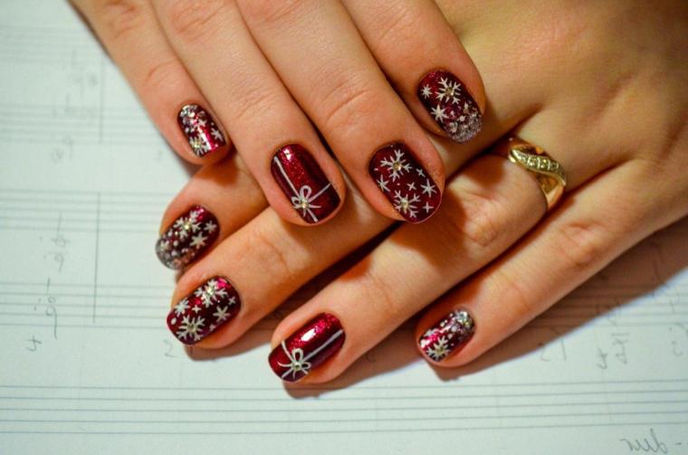 Semipermanente natalizio con unghie di colore rosso e disegno di stelle