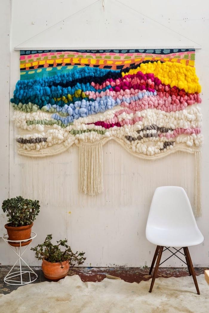 Salotto con piante e una decorazione da parete colorata e con frange