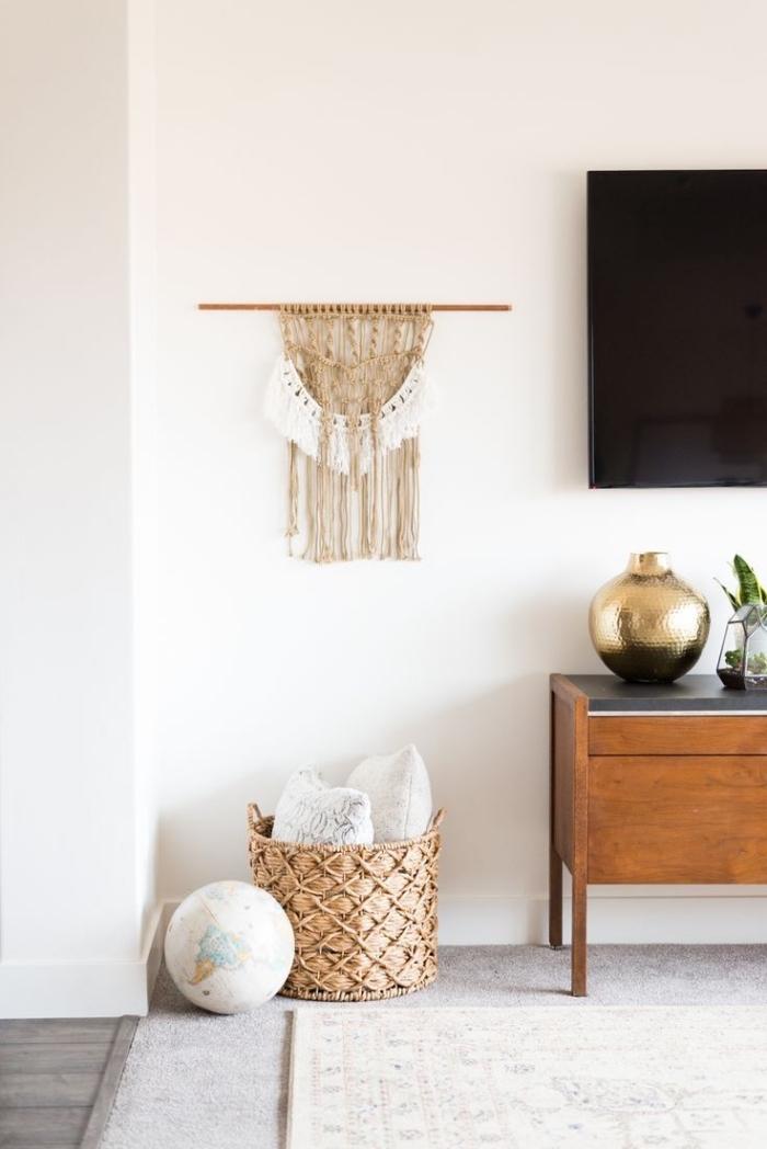 Parete del soggiorno decorata da una creazione macramè sostenuta da un bastone di legno