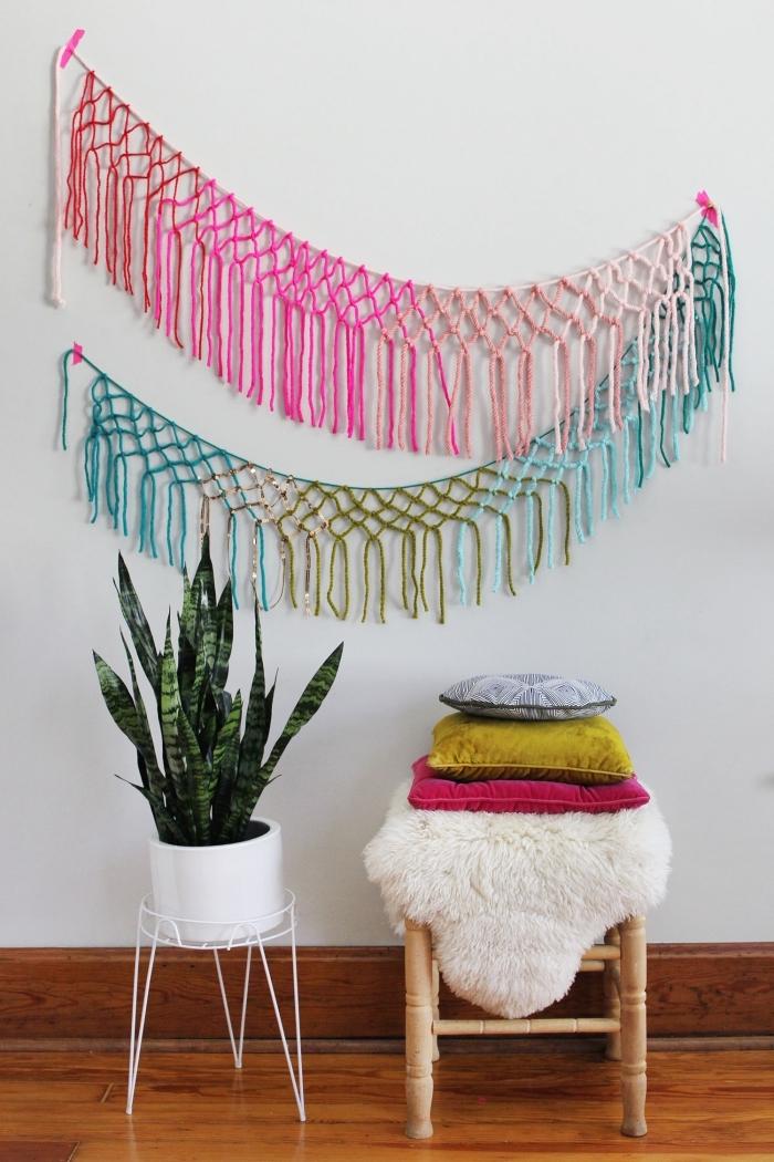 Parete bianca decorata con un macramè colorato di tre file di nodi semplici