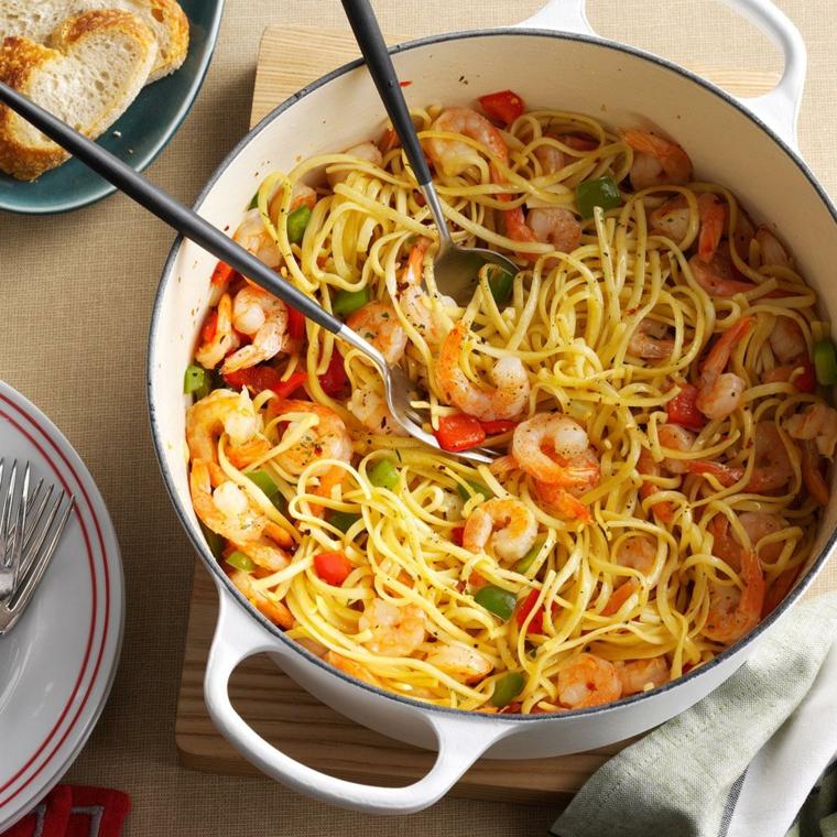 Pentola con spaghetti ai gamberetti e verdure tagliate a pezzettini