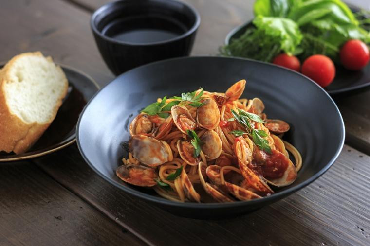 Cena della vigilia con un piatto si spaghetti alle vongole e sugo rosso di pomodoro
