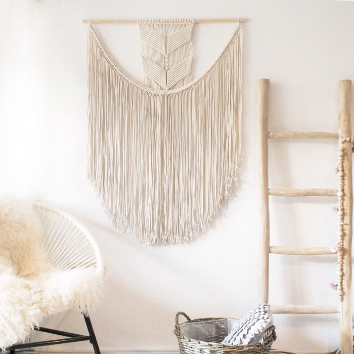 Soggiorno con una sedia in rattan e decorazione da parete con macramè di frange