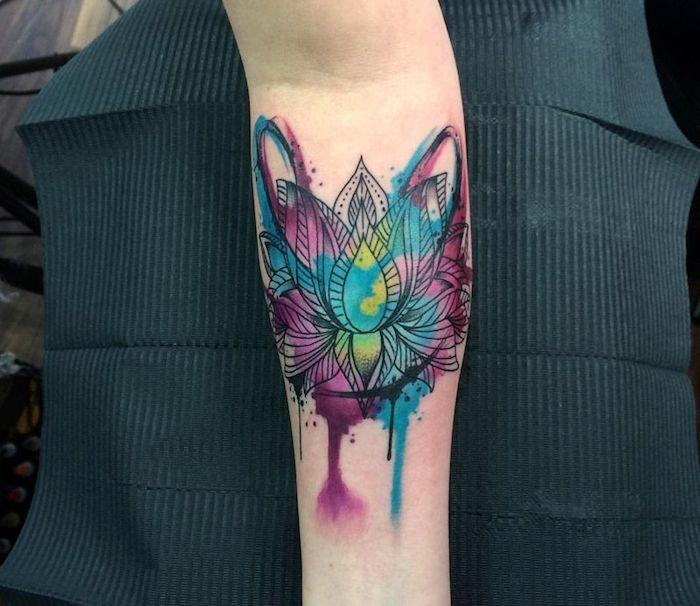 Il disegno di un fiore di loto colorato sull'avambraccio di una donna