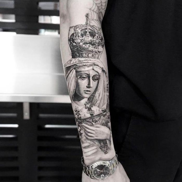 Il braccio di un uomo con un grande tattoo religioso con donna e croce in mano