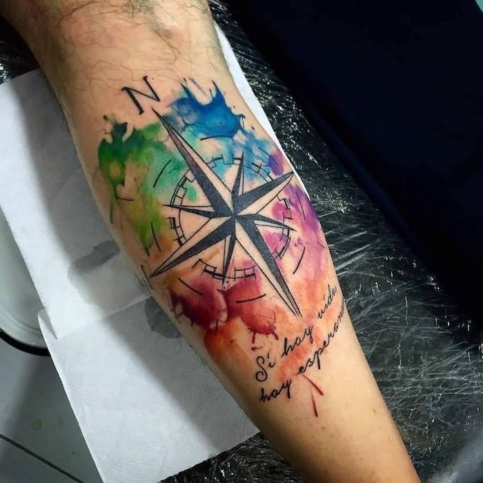 Idea per un tatuaggio braccio uomo con disegno colorato di una bussola con scritta