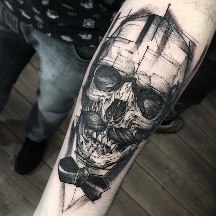 Tatto uomo braccio con il disegno di un teschio con baffi sull'avambraccio