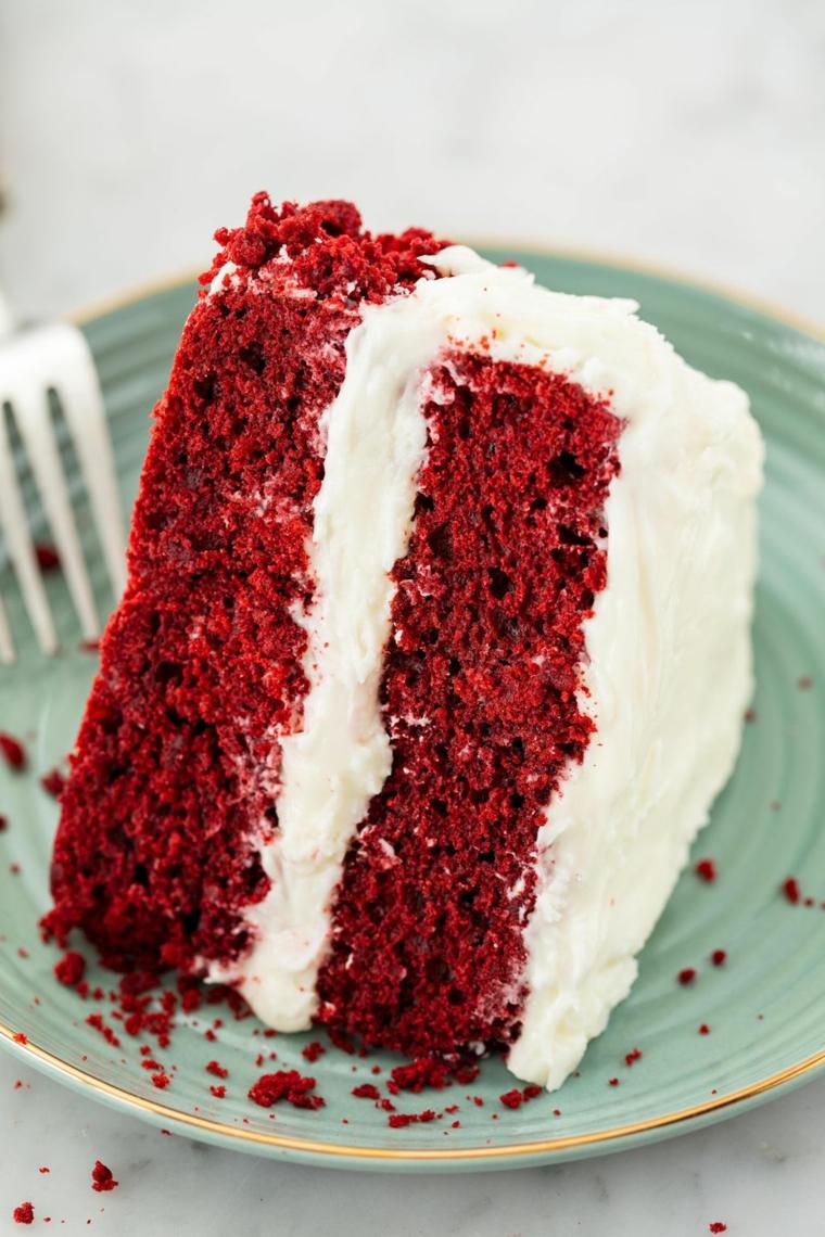 Una fetta di torta natalizia con strati di colore rosso e panna montata