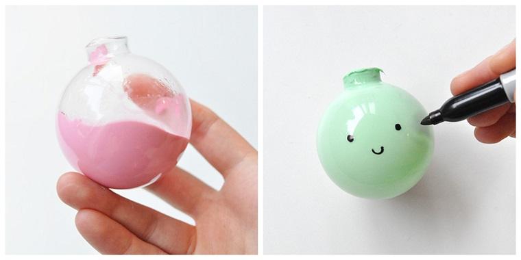 Addobbi natalizi fai da te con una pallina di plastica trasparente dipinta di colore rosa e verde