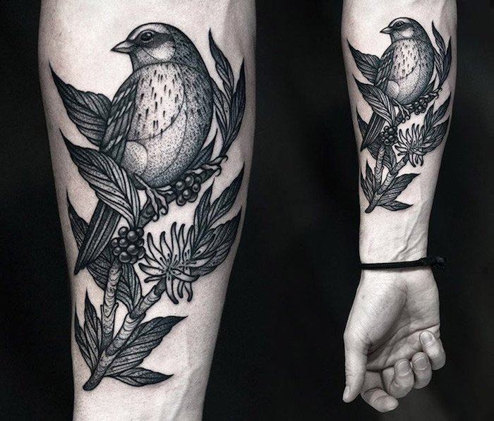 Il braccio di un uomo con il disegno di un uccello su rami con foglie