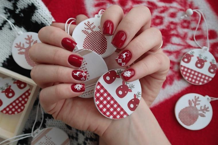 Vari ornamenti natalizi e una manicure di colore rosso con sticker