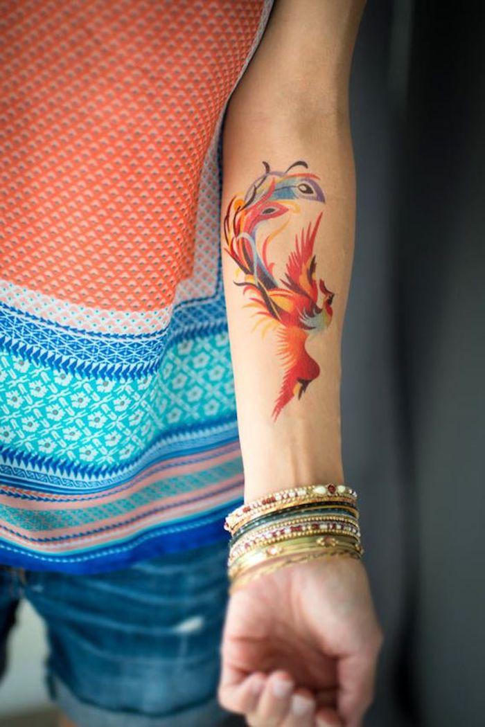 Un tattoo temporaneo con disegno di piume colorate sull'avambraccio di una donna