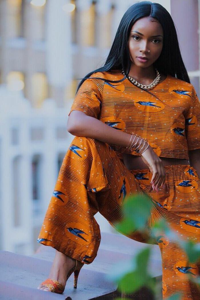 Moda femminile con stoffe colorate, ragazza con capelli neri lisci, top corto e pantalone arancione