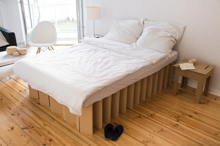 Mobili fai da te con il cartone, camera da letto con pavimento in legno e biancheria di colore bianco
