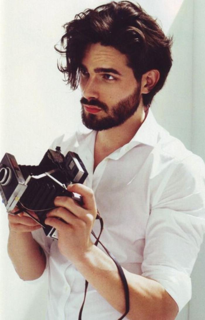 Ragazzo che tiene una macchina fotografica in mano, acconciature maschili dall'effetto mosso