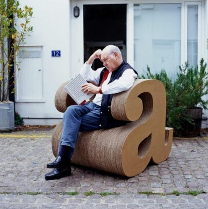 Un uomo seduto su una sedia di cartone, costruire un mobile da giardino
