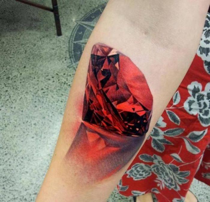Tattoo di un diamante rosso sull'avambraccio di una donna, tatuaggi piccoli colorati