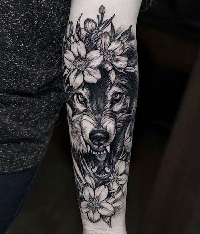 Tatuaggi femminili e un'idea con disegno di un lupo con fiori sull'avambraccio