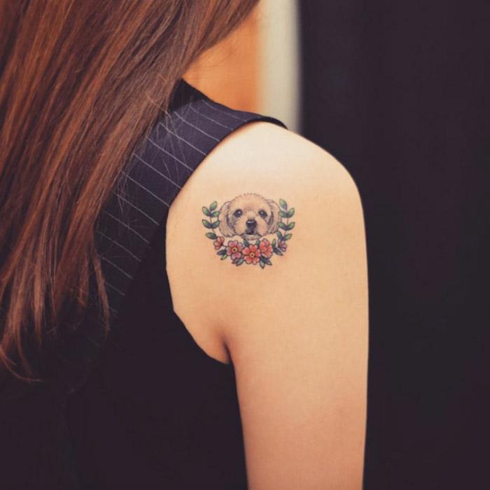 Tattoo piccolo con la faccia di un cagnolino sulla spalla di una donna