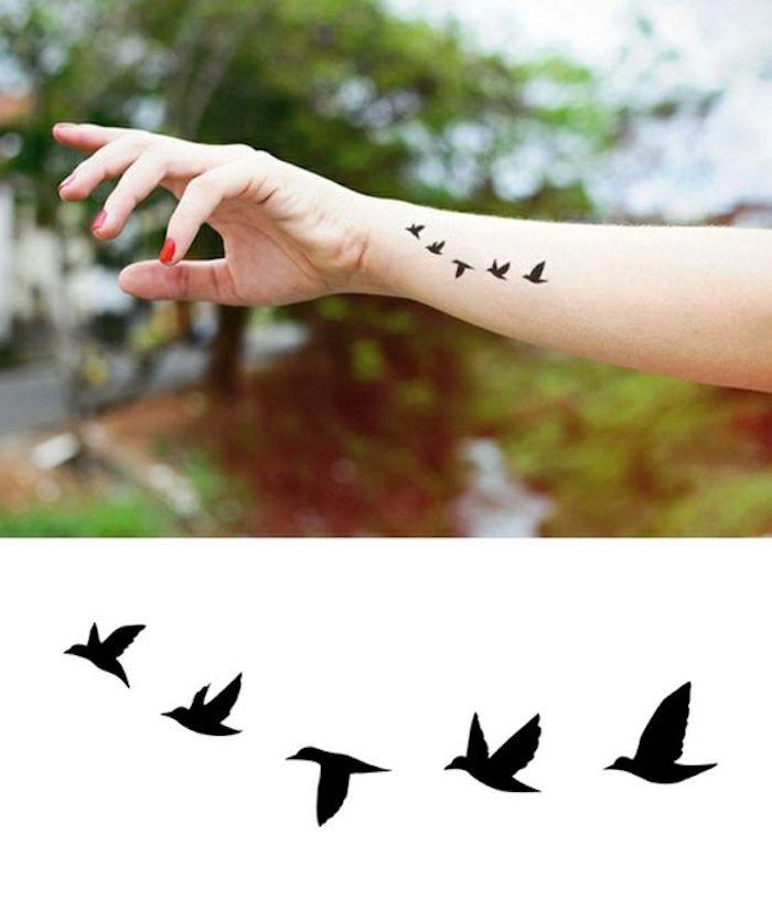 Piccolo tattoo con rondini sul polso della mano di una donna