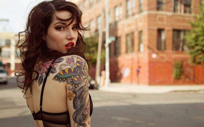 Donna rockabilly con un tatuaggio colorato con fiori e farfalle