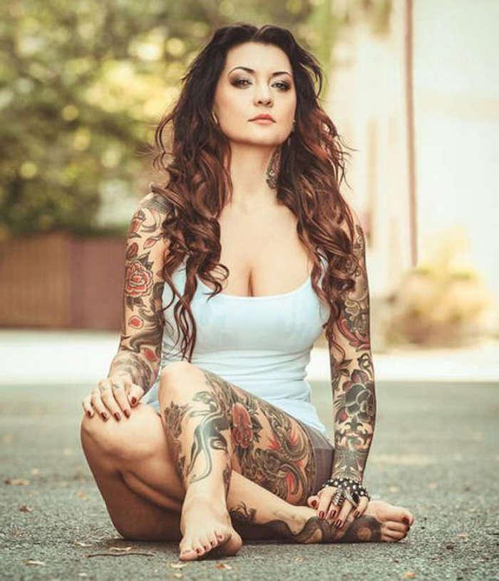 Una donna ricoperta di tatuaggi floreali colorati sulle gambe e sulle braccia