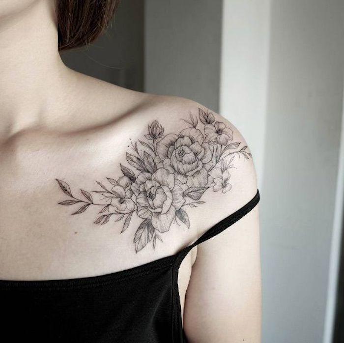 Disegni tatuaggi con fiori, la spalla di una donna con un tattoo floreale